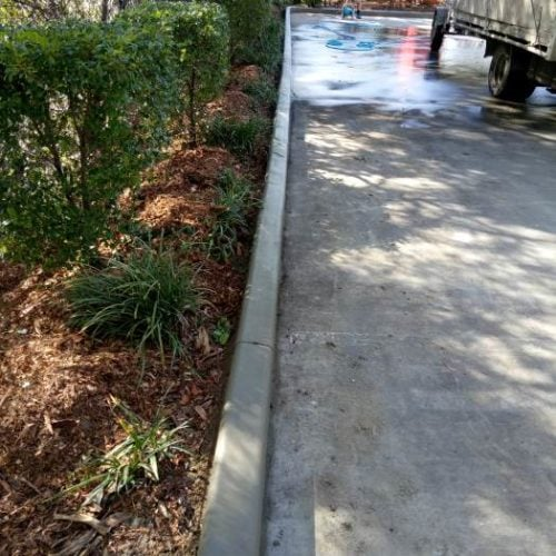 Continuous concrete driveway edging kerb with garden bed