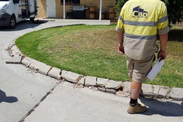 Broken continuous concrete driveway edging kerb before being repaired